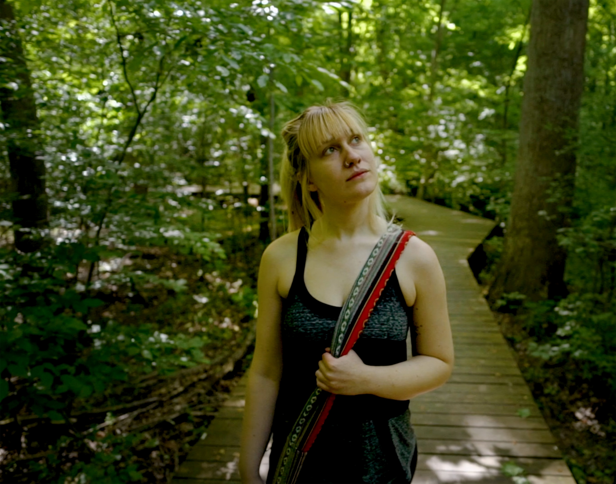 Photo of a young woman enjoying a nature walk on one of Cary, NC's greenways.