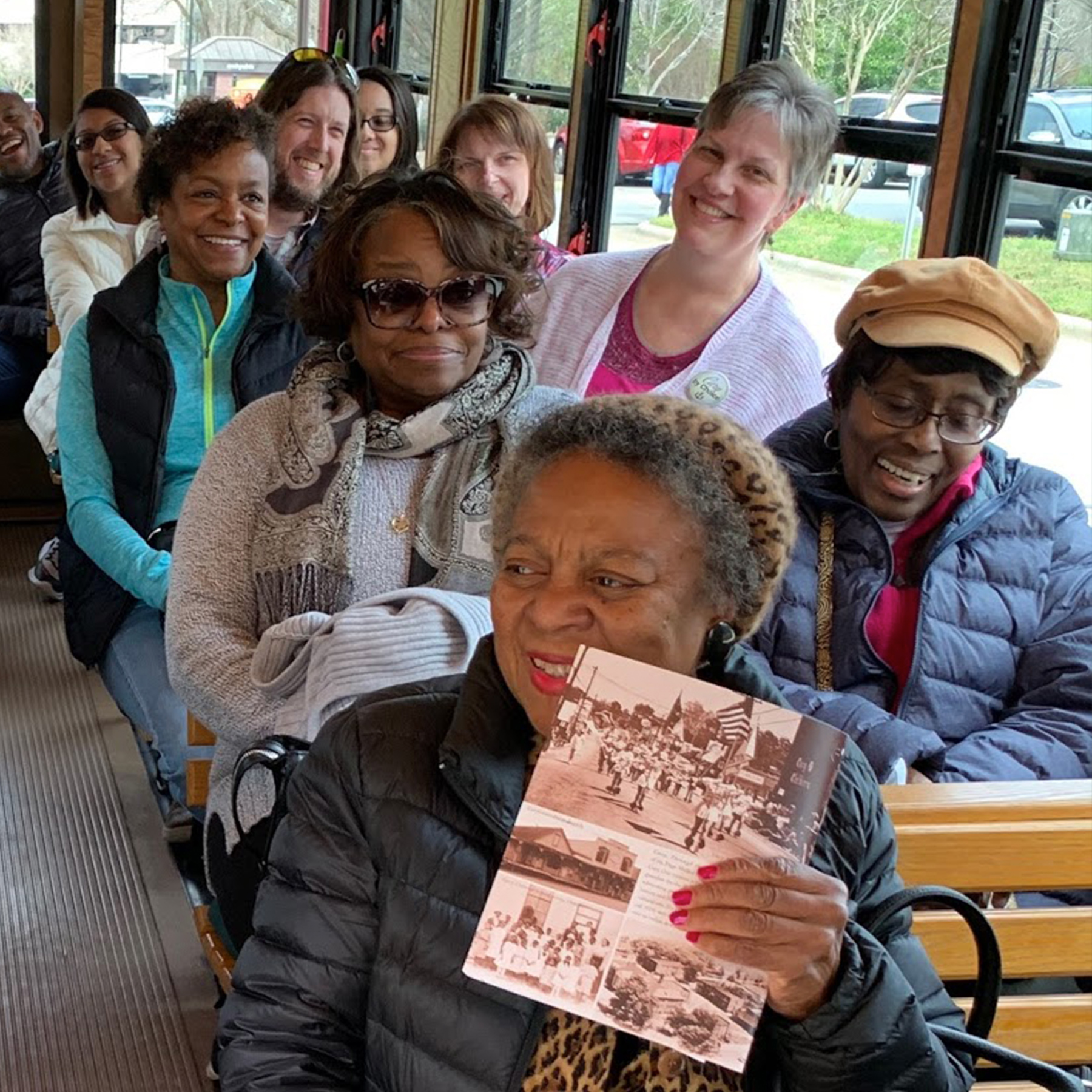 Photo of an African American woman sitting on a tour bus holding a pamphlet.